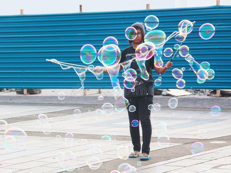 Малайзийская девушка делает большие пузыри в месте Kuching общественном внешнем стоковые фото