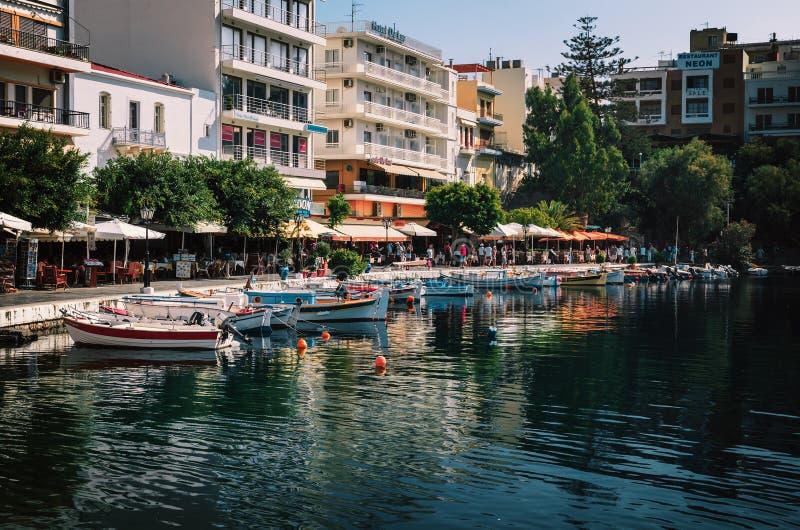 Малая гавань с причаленными рыбацкими лодками на городке Aghios Nikolaos на острове Крита, Греции стоковые изображения