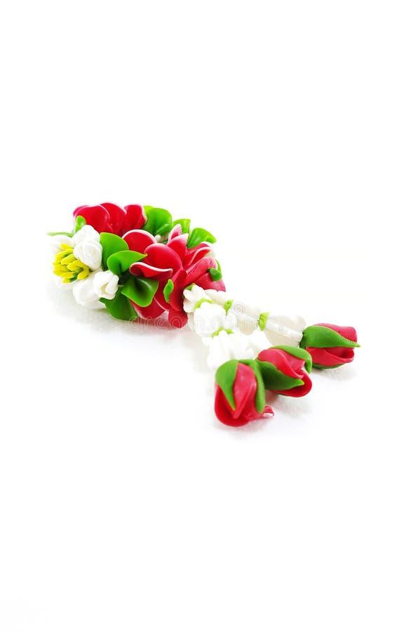 Малая гирлянда глины полимера цветков на белой предпосылке стоковая фотография