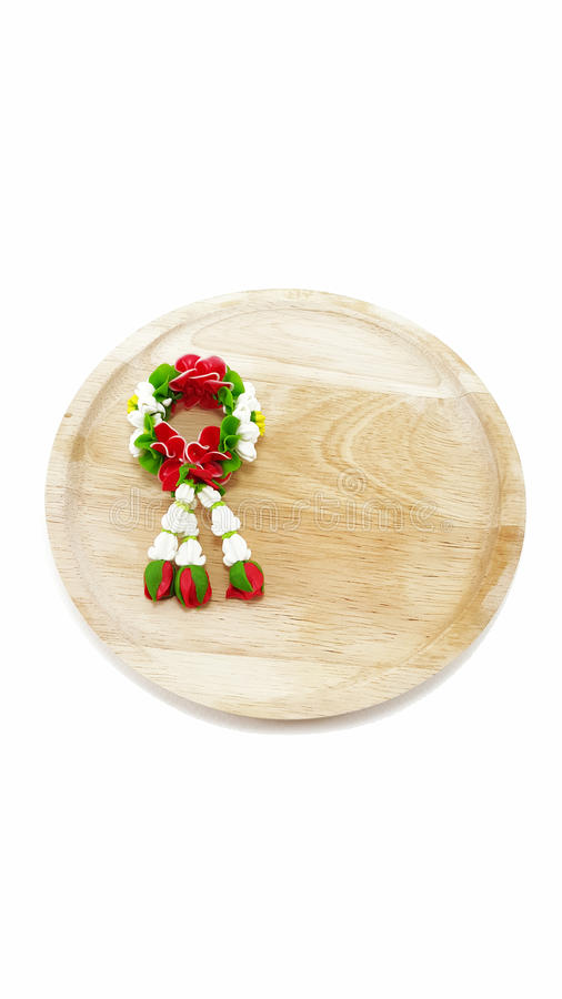 Малая гирлянда глины полимера цветков на деревянной плите в белой предпосылке стоковая фотография
