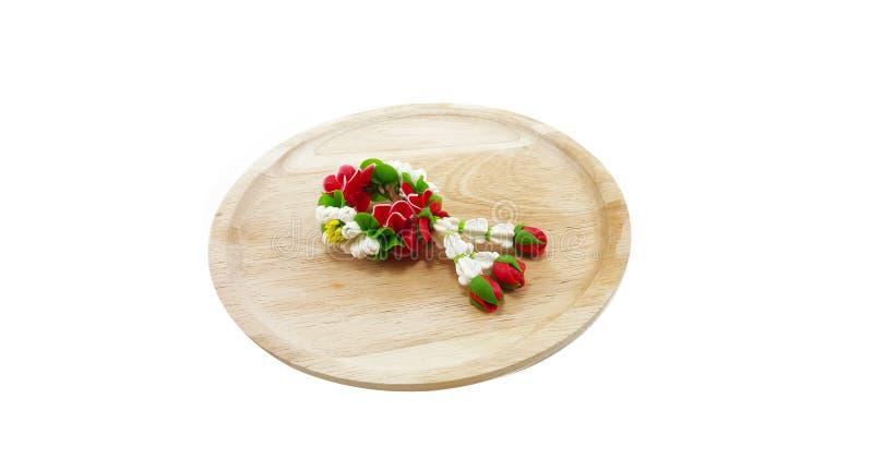 Малая гирлянда глины полимера цветков на деревянном подносе; задняя часть белизны стоковое фото rf