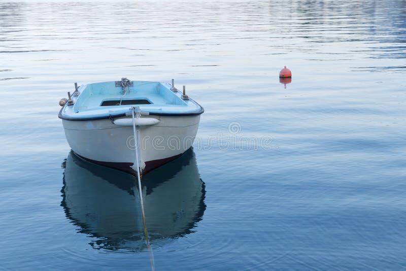 Малая голубая рыбацкая лодка в спокойной воде стоковые фотографии rf