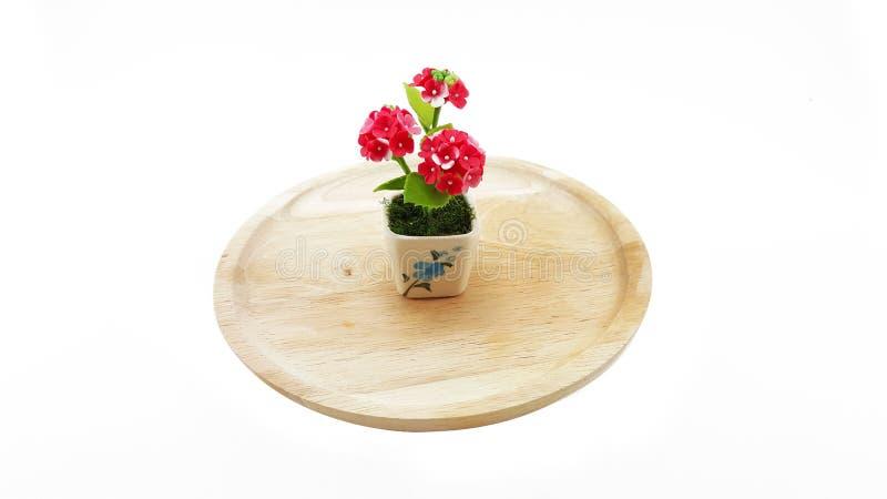 Малая глина полимера цветков на деревянной плите; белая предпосылка стоковое изображение rf