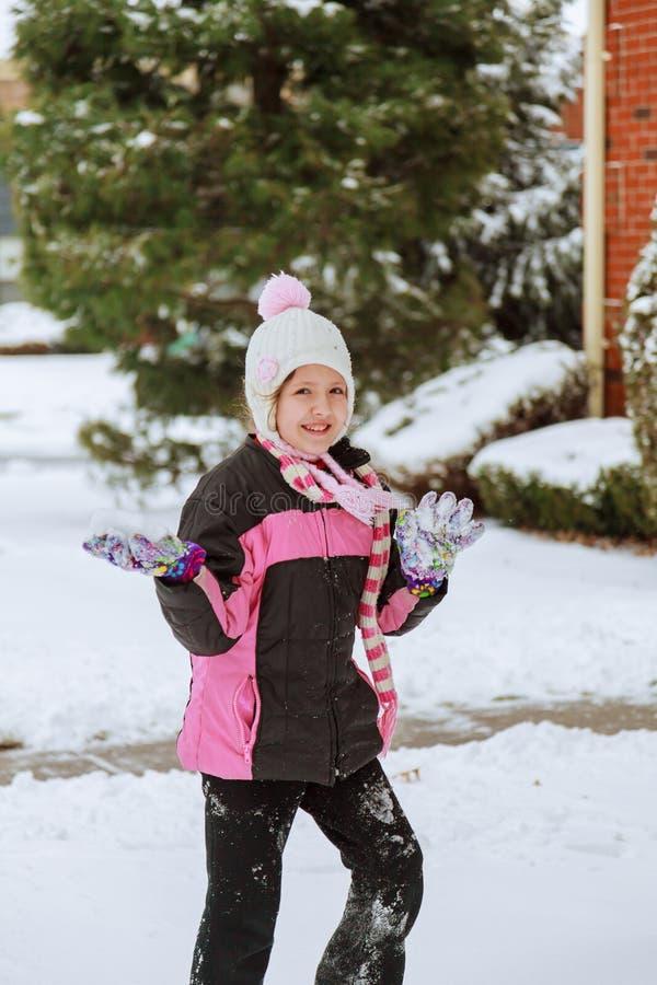 Малая девушка играя с снегом на солнечный день стоковое изображение