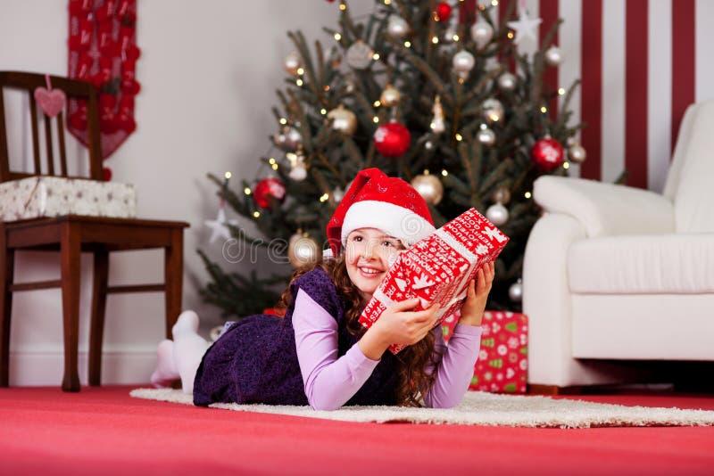 Малая девушка обнимая ее подарок на рождество стоковое изображение rf