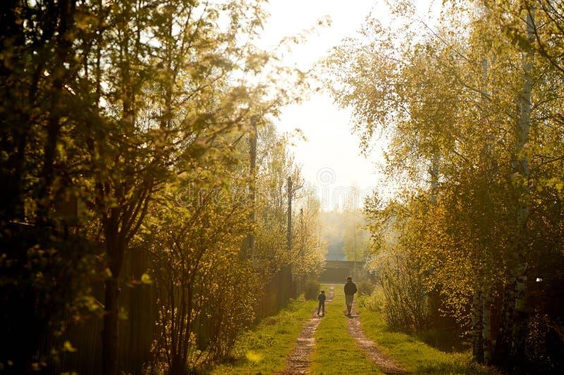 Малая диаграмма ребенка и людей на заднем плане сельский ландшафт Коттедж, праздник золотистый заход солнца стоковое изображение rf