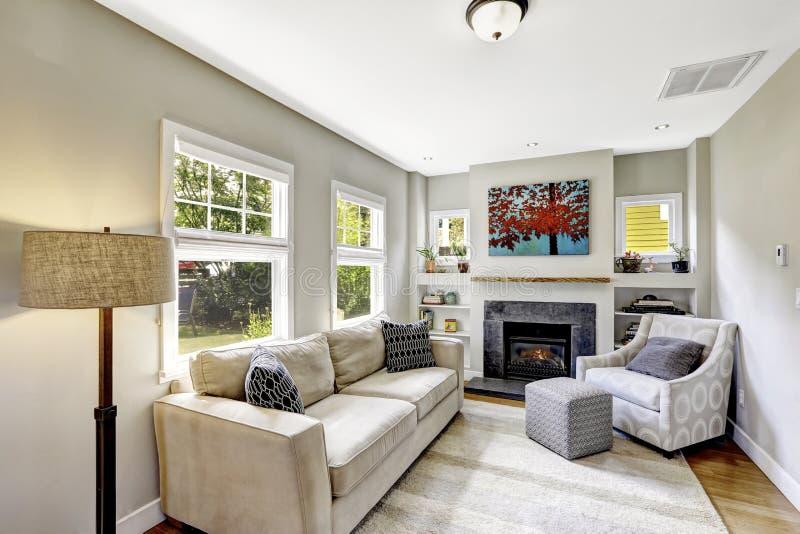 Малая но славная и уютная живущая комната с камином и софой стоковая фотография