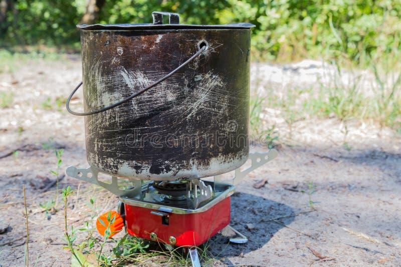 Малая располагаясь лагерем газовая плита и большой закоптелый бак стоковые фотографии rf