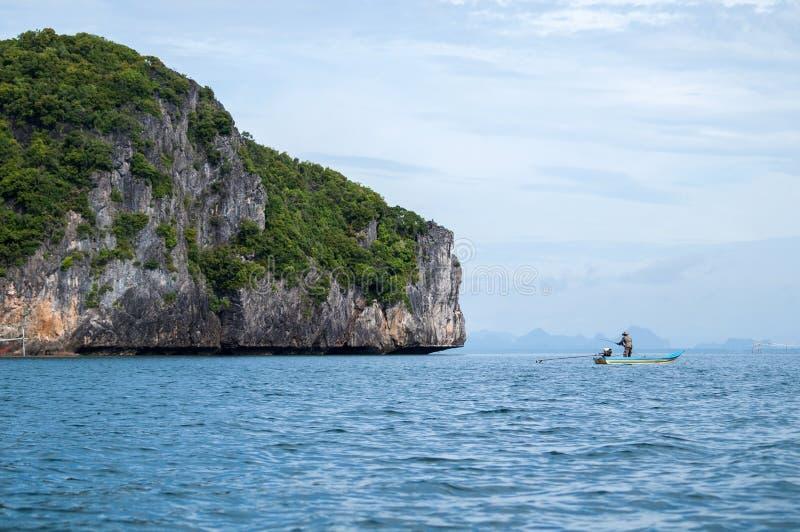 Малая шлюпка рыболова около острова утеса стоковые фото