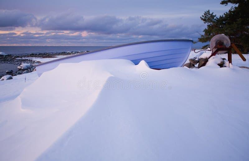Малая шлюпка строки кладя на Pebble Beach предусматриванное в снеге стоковое изображение rf