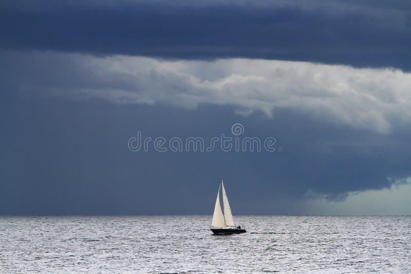 Малая яхта на большом океане и темных облаках стоковые фотографии rf
