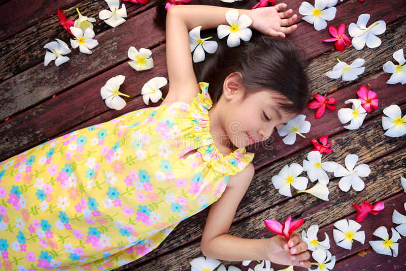 Маленькая азиатская девушка кладя на пол стоковая фотография