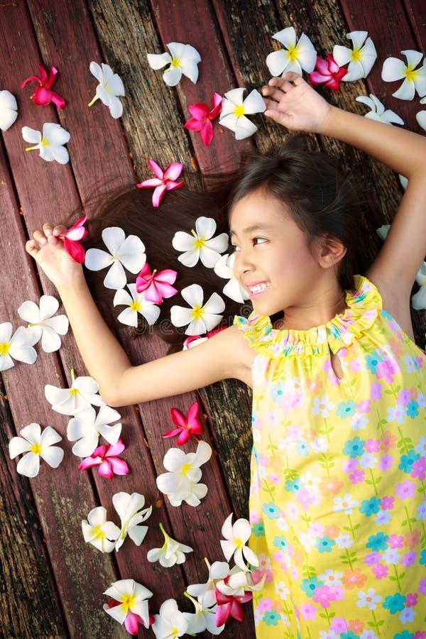 Маленькая азиатская девушка кладя на пол стоковые фотографии rf
