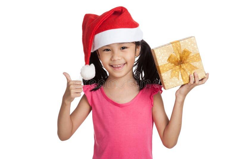 Маленькая азиатская девушка с большими пальцами руки шляпы и подарочной коробки santa вверх стоковая фотография rf