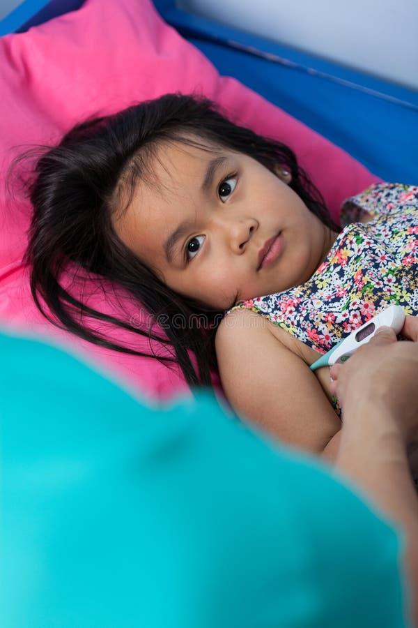 Маленькая азиатская девушка с лихорадкой стоковая фотография rf