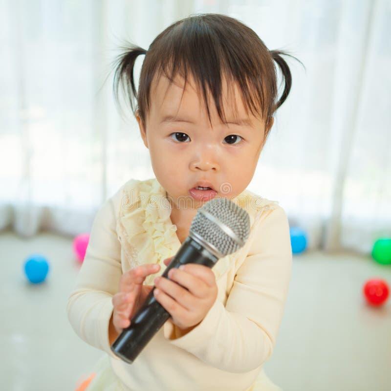 Download Маленькая азиатская девушка с микрофоном Стоковое Изображение - изображение насчитывающей бобра, невиновность: 40582565