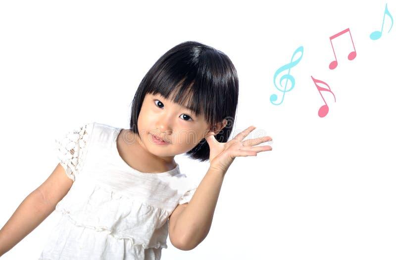 Маленькая азиатская девушка слушая к музыке в природе стоковые фото