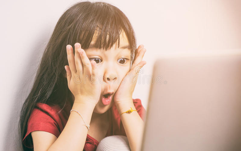 Маленькая азиатская девушка удар с чего она видит на интернете стоковое фото rf