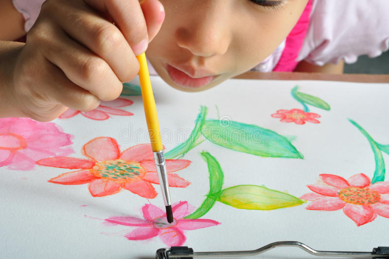 Маленькая азиатская рука девушки красит ее изображение акварели стоковые фотографии rf