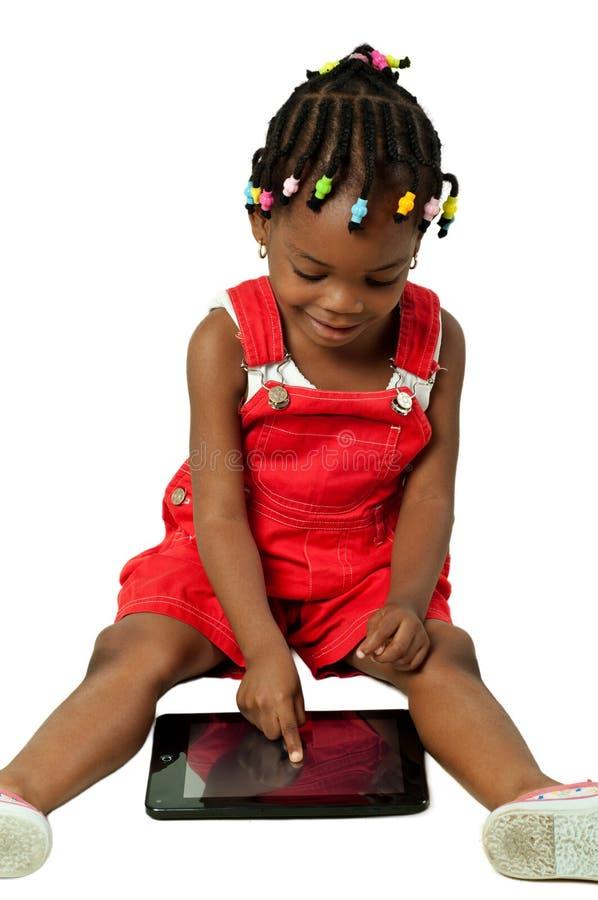 Маленькая Афро-американская девушка используя ПК таблетки стоковая фотография rf
