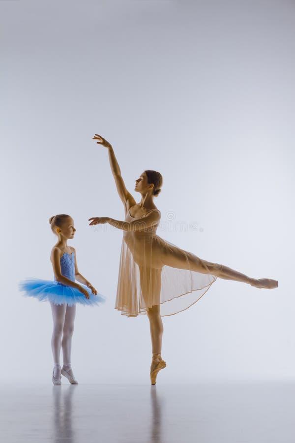 Маленькая балерина представляя с личным учителем стоковые фото