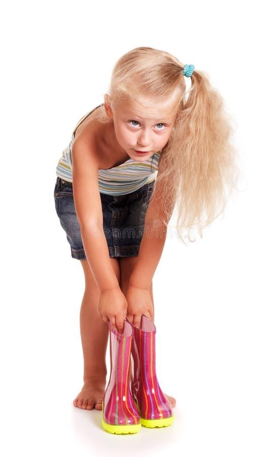 Маленькая белокурая девушка гнуть вниз с держать резиновые ботинки изолированный стоковые фото