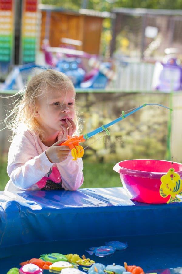 Маленькая белокурая девушка играя в парке стоковое изображение rf