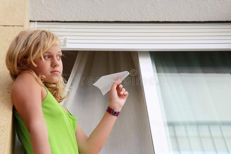 Маленькая белокурая кавказская девушка с самолетом бумаги в окне стоковые фото