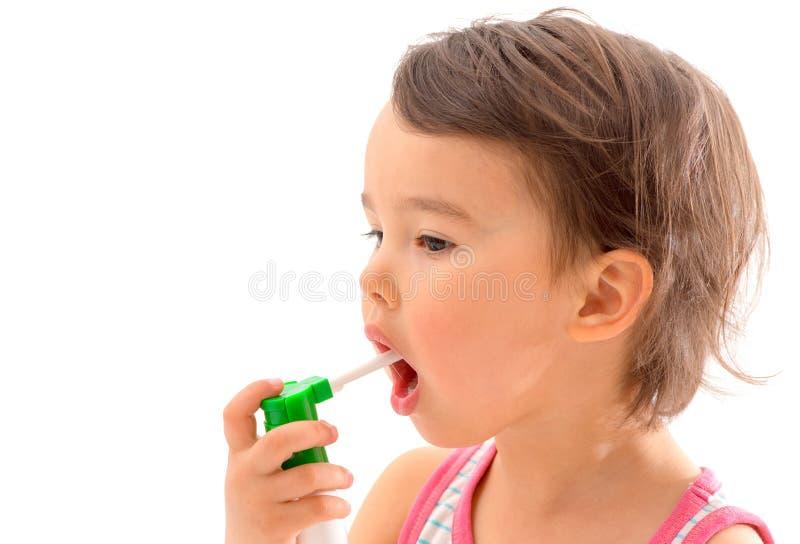 Маленькая больная девушка использовала медицинский брызг для дыхания стоковое изображение rf