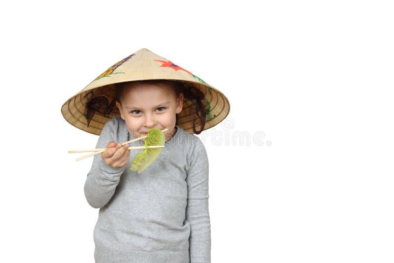 Маленькая въетнамская девушка ест салат с isolateg палочек дальше стоковое фото rf