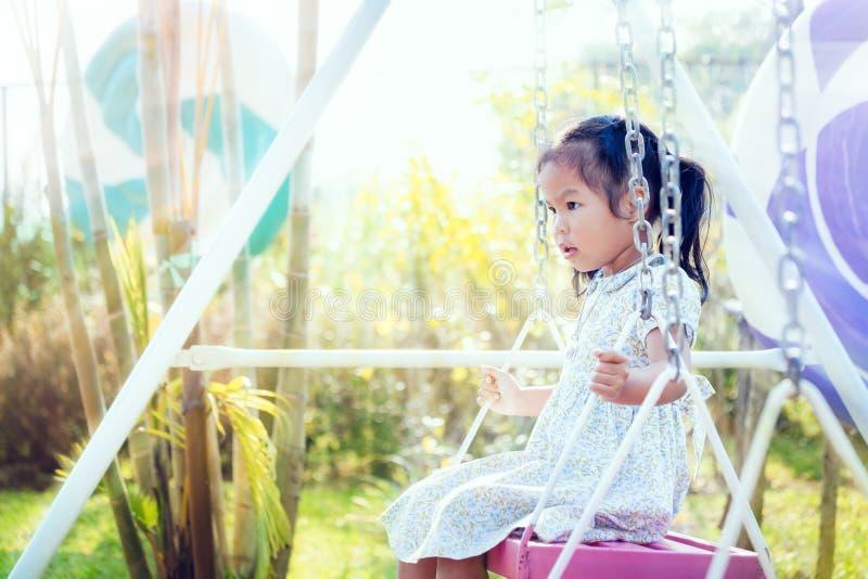 Маленькая девочка Азии играет качание на задворк в солнечном дне стоковая фотография rf