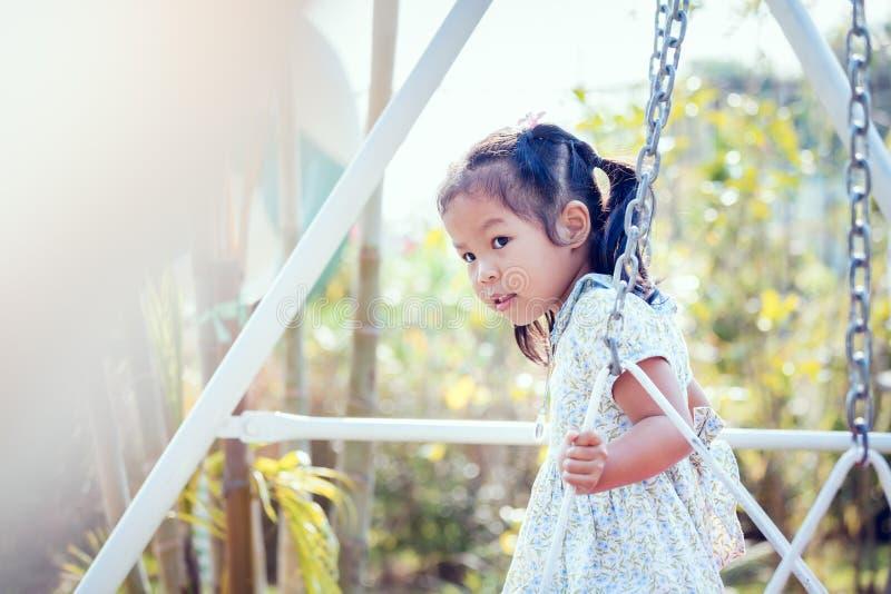 Маленькая девочка Азии играет качание на задворк в солнечном дне стоковое фото rf