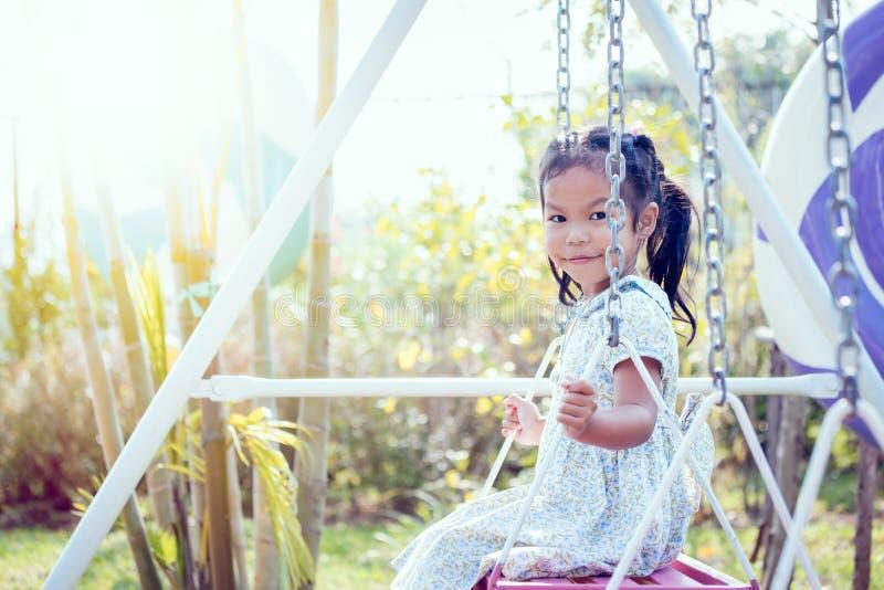 Маленькая девочка Азии играет качание на задворк в солнечном дне стоковое изображение rf