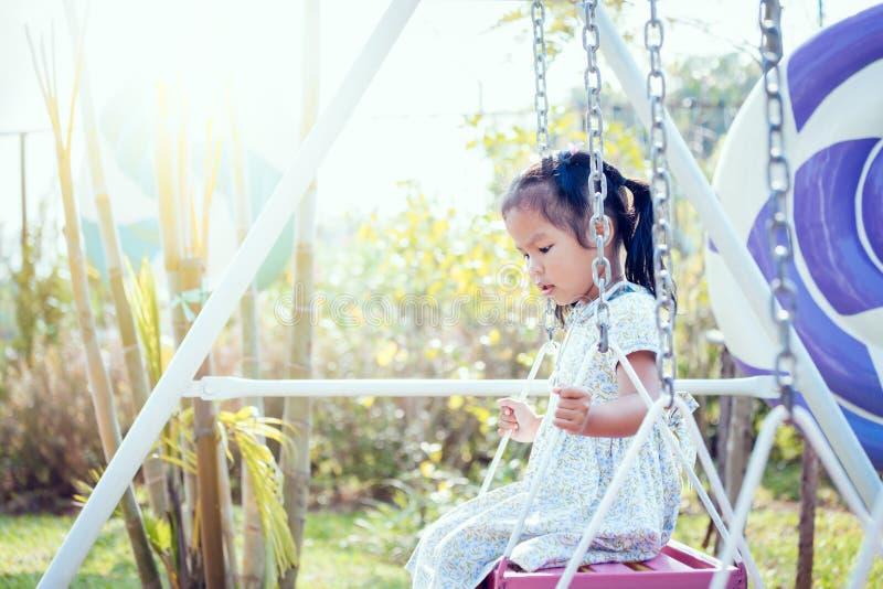 Маленькая девочка Азии играет качание на задворк в солнечном дне стоковая фотография