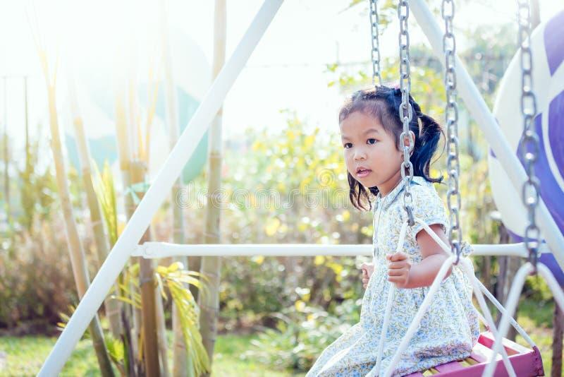 Маленькая девочка Азии играет качание на задворк в солнечном дне стоковые изображения