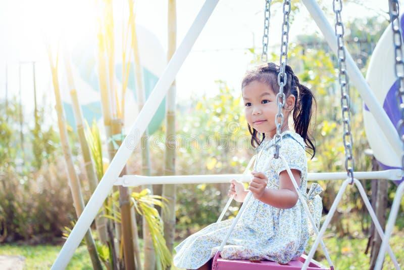 Маленькая девочка Азии играет качание на задворк в солнечном дне стоковые изображения rf