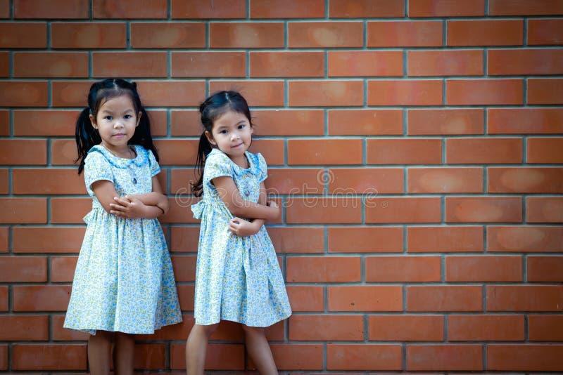Маленькая девочка Азии стоя с кирпичной стеной стоковое фото