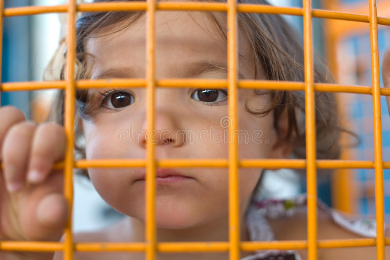 Маленькая девочка внутри клетки стоковое изображение