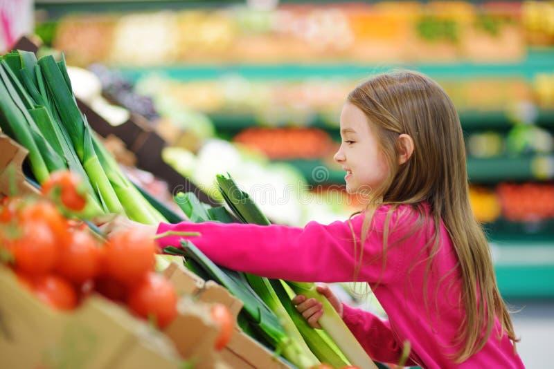 Маленькая девочка выбирая свежий лук-порей в продовольственном магазине стоковое изображение