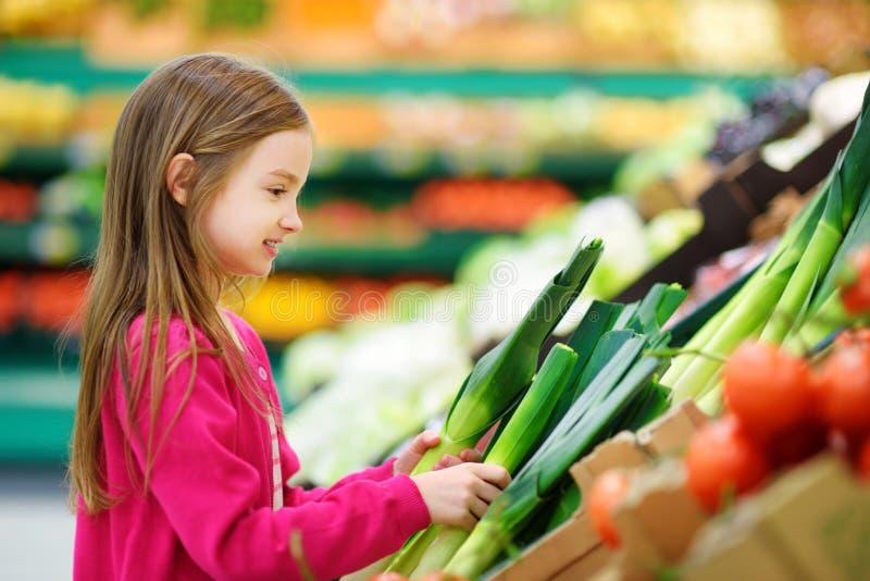 Маленькая девочка выбирая свежий лук-порей в продовольственном магазине стоковое изображение rf