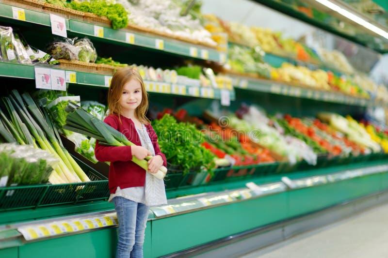 Маленькая девочка выбирая лук-порей в магазине стоковое фото
