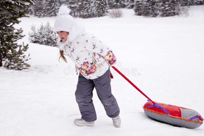 Маленькая девочка вытягивая трубопровод снега ремня стоковые изображения rf