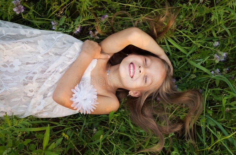 Маленькая девочка в белом платье лежа в траве и смехе стоковое фото rf