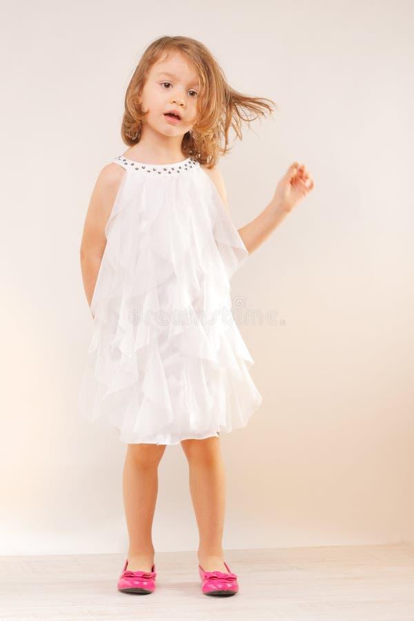 Маленькая девочка в белом платье и розовых ботинках стоковые фотографии rf