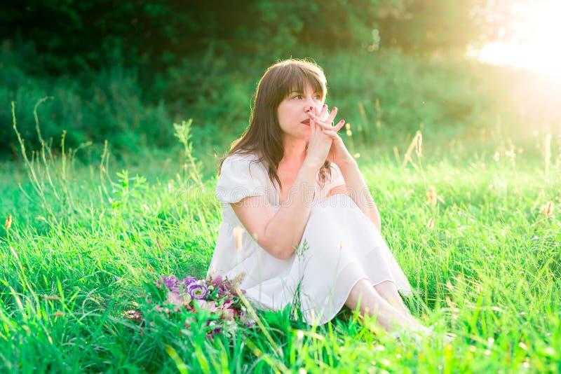 Маленькая девочка в белом платье сидя в середине поля и отражает Тоскливость, одиночество, сомнение стоковое фото rf