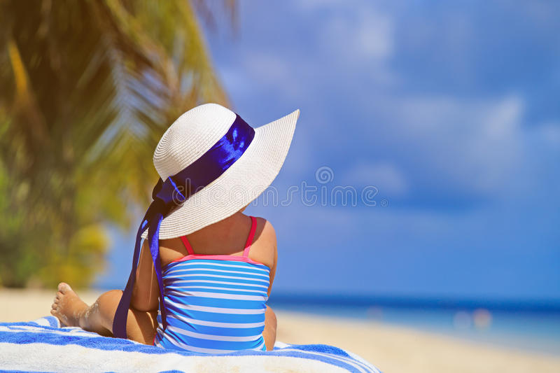 Маленькая девочка в большой шляпе на пляже лета стоковые фото