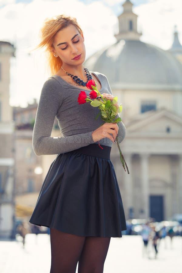 Маленькая девочка в влюбленности Белокурый подросток с розами в руке стоковые изображения