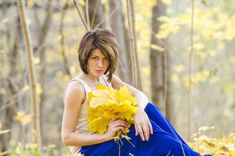 Маленькая девочка в лесе осени с букетом mapple выходит стоковые фото