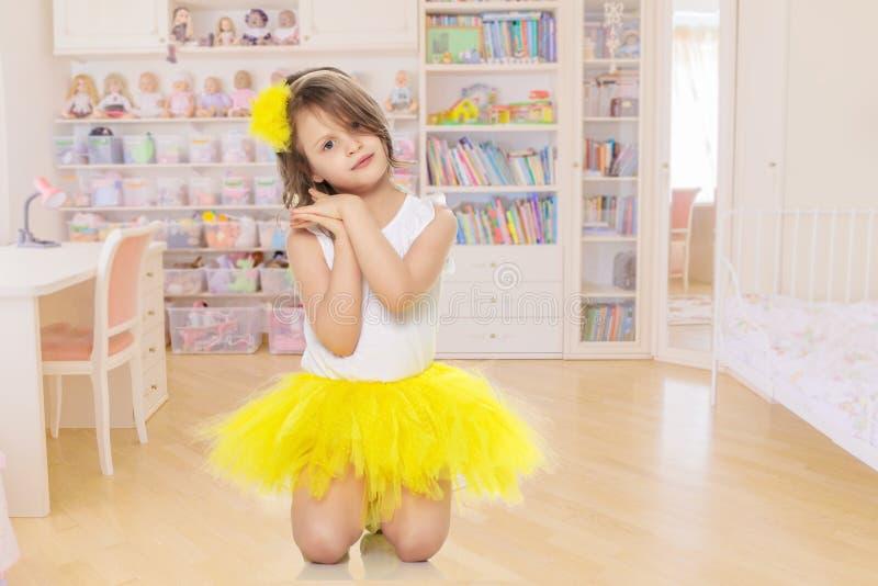 Маленькая девочка в желтой юбке и белой футболке стоковые изображения