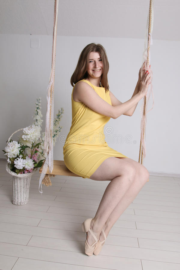 Маленькая девочка в желтом платье на качании в комнате стоковое фото
